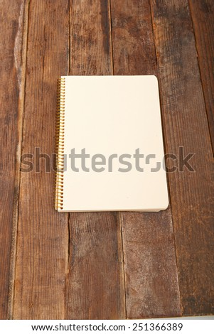 Open notepad with empty white pages laying on a wooden table - stock photo