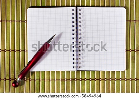 Open notepad with pen over textured bamboo mat for scrapbook related purposes - stock photo
