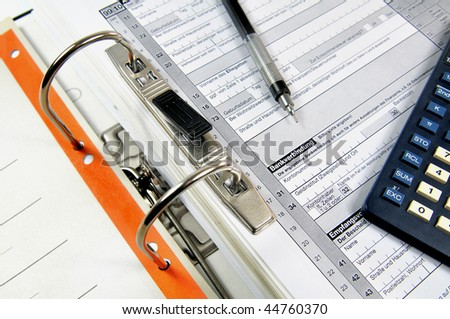 Open office ring-binder with tax documents, ball pen and calculator - stock photo