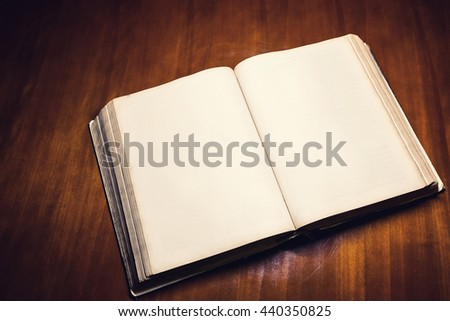Open old Bible on a wooden background - stock photo