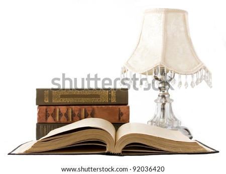 Open old book, book stack and vintage lamp isolated on white - stock photo