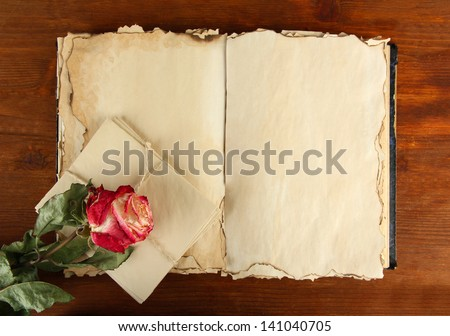 Open old book, letters and rose on wooden background