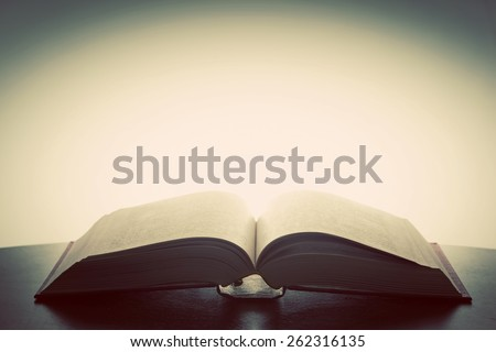 Open old book, light from above. Fantasy, imagination, education concept. Vintage mood. - stock photo