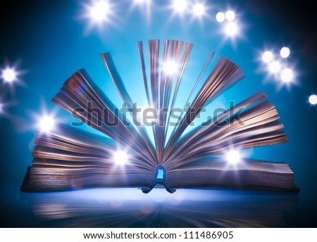 Open old book, mystical blue light at background, light painting - stock photo
