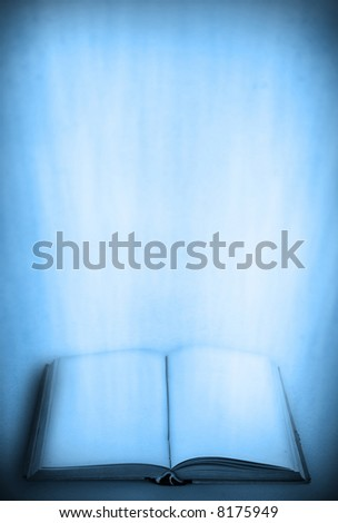 open old book with light beams against retro background in blue tones