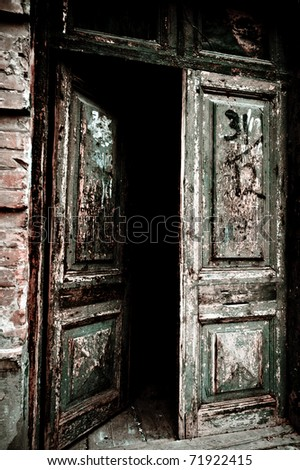 Open old door leading into a dark entrance - stock photo