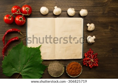 open old vintage book with berries, tomatoes, Chile peppers, spices and grape leaf on wooden background. Healthy vegetarian food. Recipe, menu, mock up, cooking. - stock photo