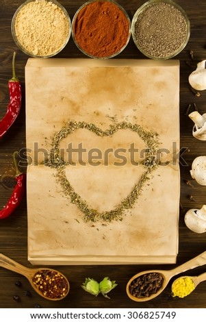 open old vintage book with spices and heart on wooden background. Healthy vegetarian food. Recipe, menu, mock up, cooking. - stock photo