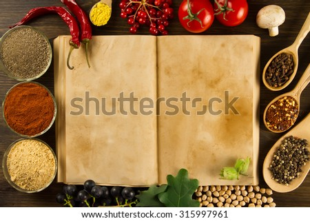open old vintage book with spices on wooden background. Healthy vegetarian food. Recipe, menu, mock up, cooking.