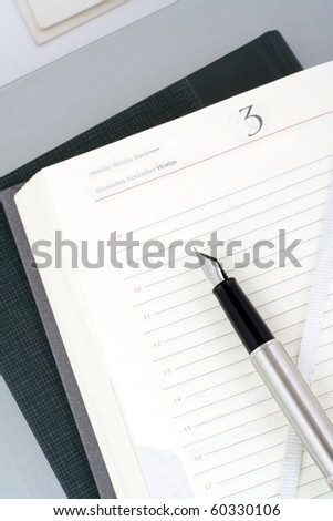 Open organizer and silver pen. Still life. - stock photo