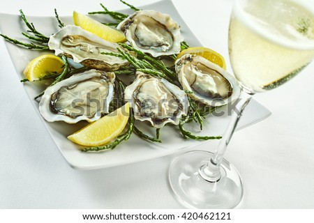 Open oyster shells with lemon wedges in plate with curled edges and drink in tall champagne glass over white - stock photo