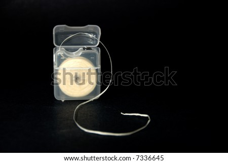 Open package of dental floss against black background. - stock photo