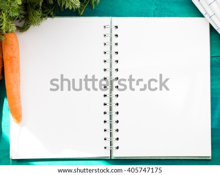 Open paper note book with blank pages on dark green table with paddock carrots and a napkin at the sides  - stock photo