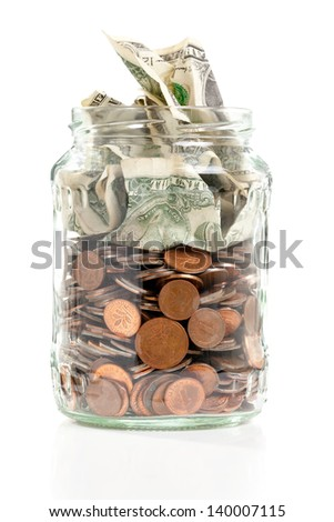 Open penny jar with bank notes over white background - stock photo