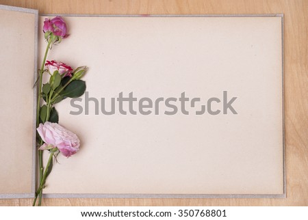 open photo album on a table and three roses - stock photo