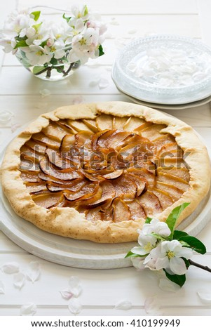 Open pie or galette with apples decorated apple blossom on white wooden desk - stock photo
