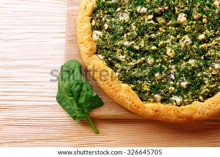 Open pie with spinach on table close up - stock photo