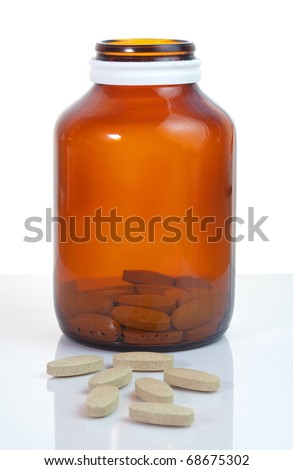Open pill bottle with medicine spilling out - stock photo