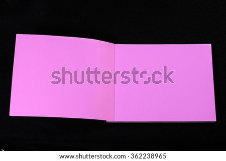 Open pink note book double page spread with blank pages on black  - stock photo