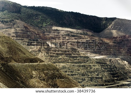 Open pit mine and roads in the side of a mountain with pine trees - stock photo