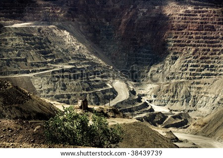 Open pit mine with a single lonely tree and rusty water tank  in the foreground - stock photo