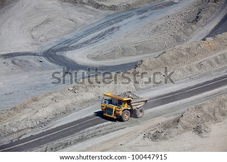 Open pit mine with supersize car - stock photo