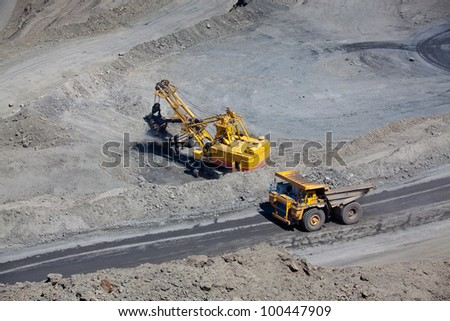 Open pit mine with supersize car and excavator - stock photo