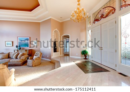 Open plan of luxury hallway and living room. White entrance door well matched with  beige concrete floor and walls - stock photo
