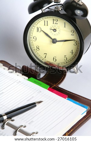 open planner with a pen and an alarm clock - stock photo