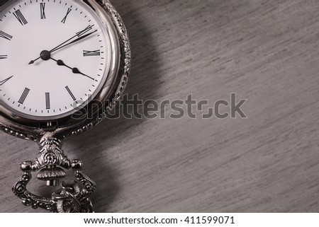 open pocket watch and chain lie on a light wooden table background, arrow on the clock, arrows on pocket watches show time of day, dial with roman numerals, copyspace, metal clock  - stock photo