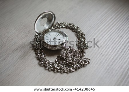 open pocket watch and chain lie on a light wooden table background,  arrow on the clock, arrows on pocket watches show time of day, dial with roman numerals   - stock photo