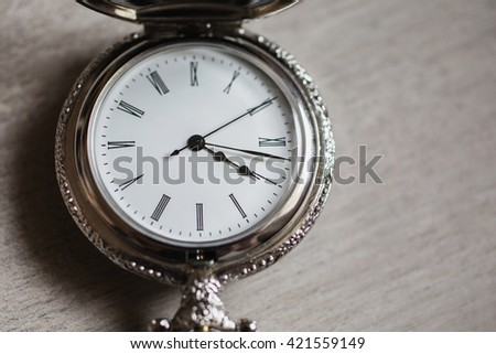 open pocket watch and chain lie on a light wooden table background,  arrow on the clock, arrows on pocket watches show time of day, dial with roman numerals, shiny metal clocks    - stock photo