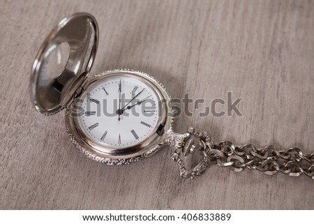 open pocket watch and chain lie on a light wooden table background, open metal vintage pocket watch on a metal chain, retro style, arrows on pocket watches show time of day, dial with roman numerals  - stock photo
