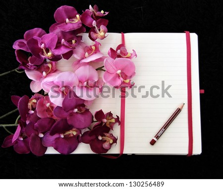 Open pocketbook with empty page and pink orchid.