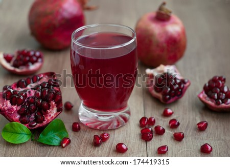 Open pomegranate with seed and pomegranate juice on wooden background - stock photo