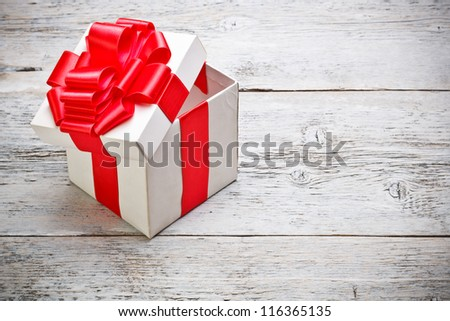 Open present box on painted wooden background - stock photo