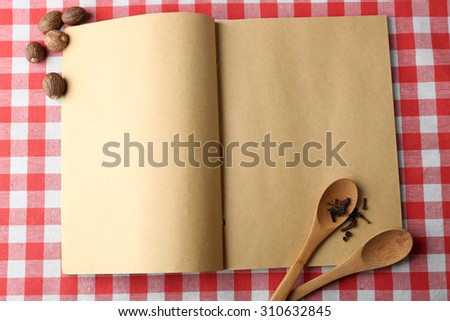 Open recipe book on color tablecloth background