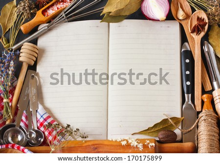 Open recipe book surrounded of food ingredients and kitchen utensils. - stock photo