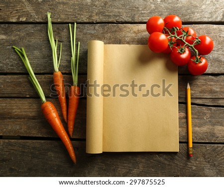 Open recipe book, vegetables on wooden background - stock photo