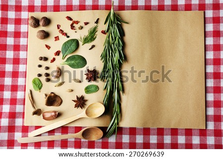 Open recipe book with fresh herbs and spices on tablecloth background - stock photo