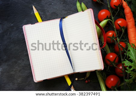 Open recipe book with fresh herbs, tomatoes and spices  - stock photo