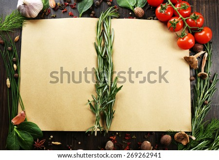 Open recipe book with fresh herbs, tomatoes and spices on wooden background - stock photo