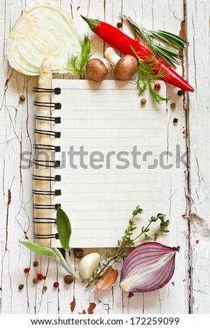 Open recipe book with vegetables and herbs on a wooden background. - stock photo