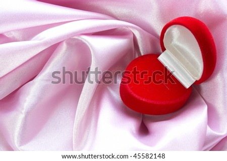 Open red heart box on pink atlas - stock photo
