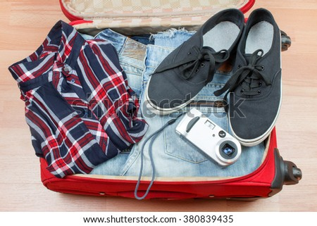 Open Red Suitcase  with Black Sneakers and old Camera. - stock photo