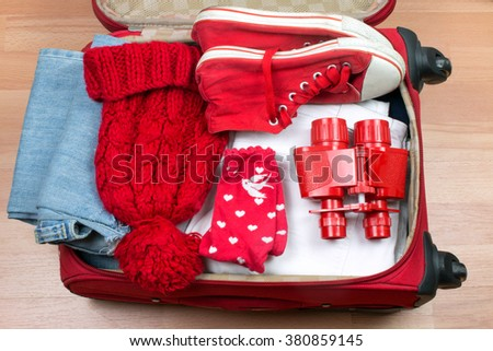 Open Red Suitcase with Red Clothes and Binoculars.
