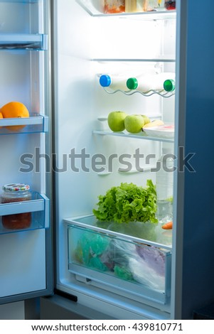 Open refrigerator full of food on kitchen at night - stock photo