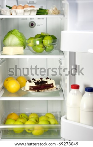 Open refrigerator full with some kinds of food - chocolate cake, lime, apples, eggs, milk - stock photo