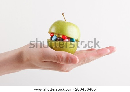 Open ripe apple full of colorful medicines - stock photo