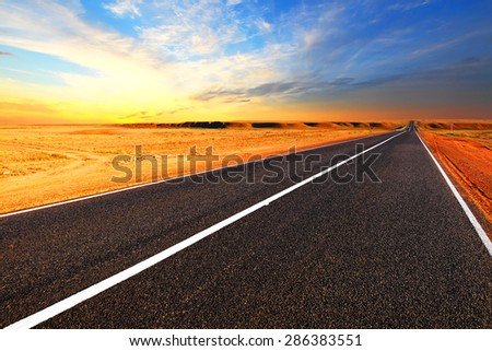 Open road.Dramatic sunset sky in the desert. - stock photo